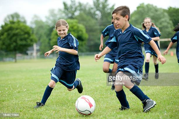 Young boys and girls playing youth soccer on grass