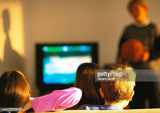Young boys and girls watching TV, boy in distance blurred.