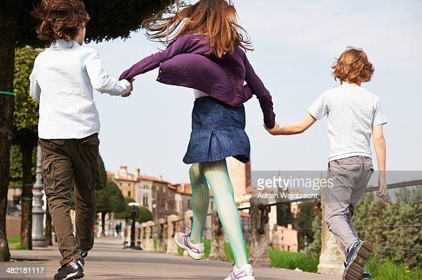 Young boys and older sister marching through park, Province of Venice, Italy