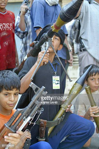 Young boys carry weapons as militiamen loyal to radical Iraqi Shiite Muslim cleric Moqtada Sadr celebrate after an attack on a police station as...