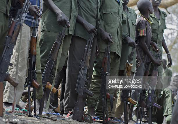Young boys children soldiers sit on February 10 2015 prepare to lay down their arms at a ceremony of the child soldiers disarmament demobilisation...