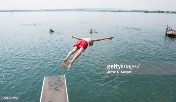 Young boys diving into the lake during the longest day of 2017 on June 21 2017 in Zug Switzerland The summer solstice was celebrated in the...