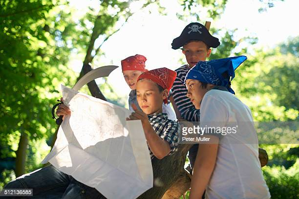 Young boys dressed as pirates, reading map