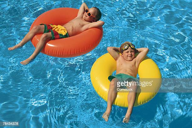 Young boys floating in inner tubes in swimming pool