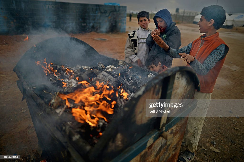 ZA'ATARI, JORDAN - FEBRUARY 01: Young boys get a heat from a burning rubbish bin as Syrian refugees go about their daily business in the Za'atari refugee camp on February 1, 2013 in Za'atari, Jordan. Record numbers of refugees are fleeing the violence and bombings in Syria to cross the borders to safety in northern Jordan and overwhelming the Za'atari camp. The Jordanian government are appealing for help with the influx of refugees as they struggle to cope with the sheer numbers arriving in the country.