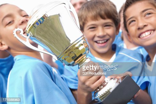 Young boys happily holding winning trophy : Stock Photo
