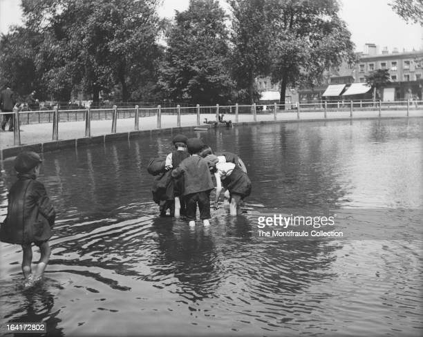 Young boys in caps playing in a pond at Clapham Common London England c1912