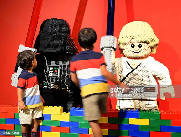 Young boys look at legomade Darth Vader and Luke Skywalker characters in the US movie 'Star Wars' at LegoLand in Tokyo on September 15 2013 The Lego...