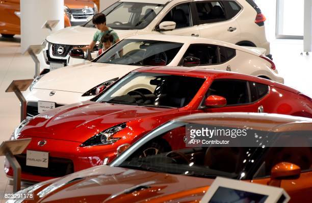 Young boys look at vehicles of Japan's automaker Nissan Motor at a showroom in Yokohama suburb of Tokyo on July 27 2017 Nissan is expected on July 27...