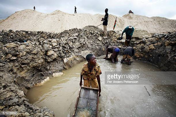 Young boys look for copper standing in a pit on December 13 2005 in Ruashi mine about 20 kilometers outside Lubumbashi Congo DRC They are some of...