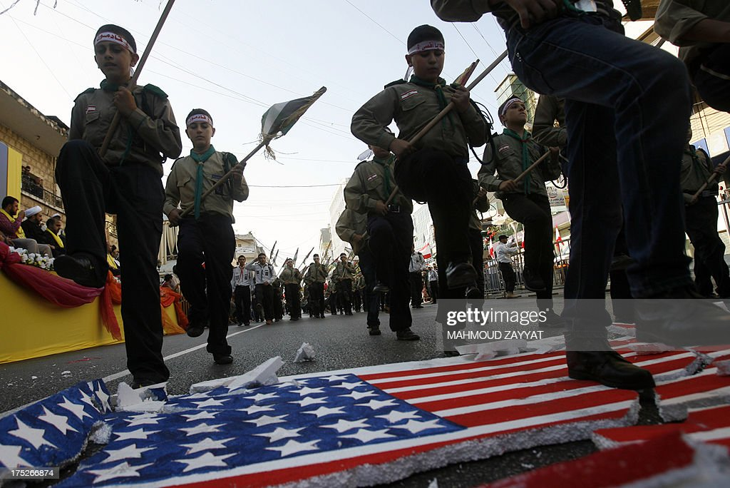 Young boys of Hezbollah's al-Mehdi scouts stomp on a polystyrene sheet bearing the American flag, during a parade in the Lebanese southern suburb of Nabatiyeh, on August 1, 2013, to mark the 'Al-Quds (Jerusalem) International Day'. An initiative started by Iranian revolutionary leader Ayatollah Ruhollah Khomeini, Quds Day is held annually on the last Friday of the Muslim fasting month of Ramadan and calls for Jerusalem to be returned to the Palestinians.