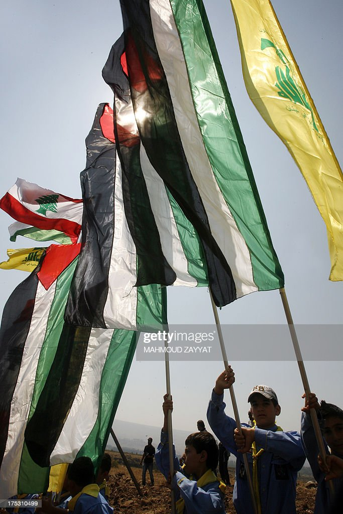 Young boys of Hezbollah's al-Mehdi scouts wave Lebanese and Palestinian flags alongside Hezbollah's flag during a parade in the southern area of Wazzani river on the Lebanese-Israeli borders, on August 2, 2013, to mark the 'Al-Quds (Jerusalem) International Day'. An initiative started by Iranian revolutionary leader Ayatollah Ruhollah Khomeini, Quds Day is held annually on the last Friday of the Muslim fasting month of Ramadan and calls for Jerusalem to be returned to the Palestinians.