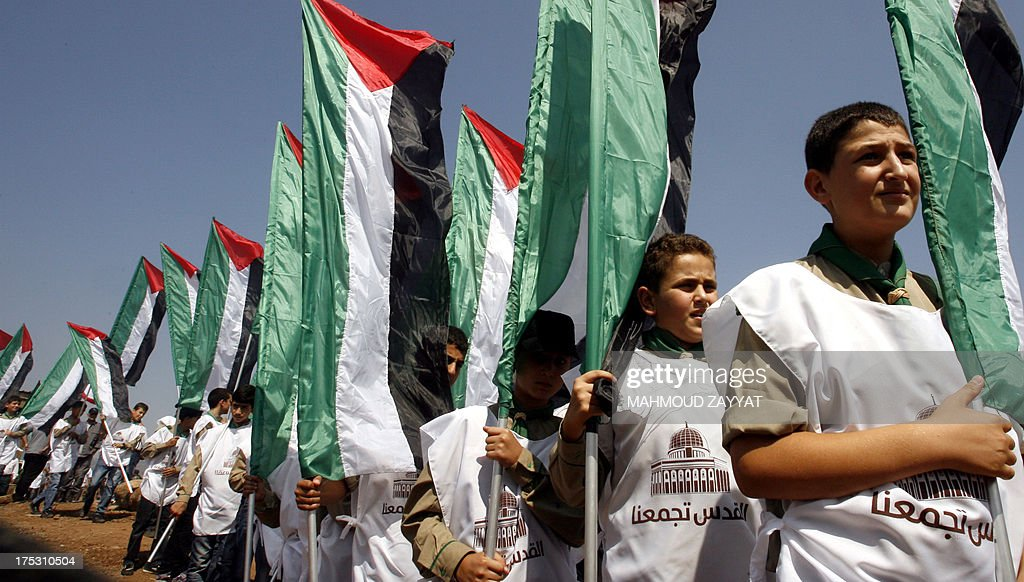Young boys of Hezbollah's al-Mehdi scouts wave the Palestinian flag during a parade in the southern area of Wazzani river on the Lebanese-Israeli borders, on August 2, 2013, to mark the 'Al-Quds (Jerusalem) International Day'. An initiative started by Iranian revolutionary leader Ayatollah Ruhollah Khomeini, Quds Day is held annually on the last Friday of the Muslim fasting month of Ramadan and calls for Jerusalem to be returned to the Palestinians.