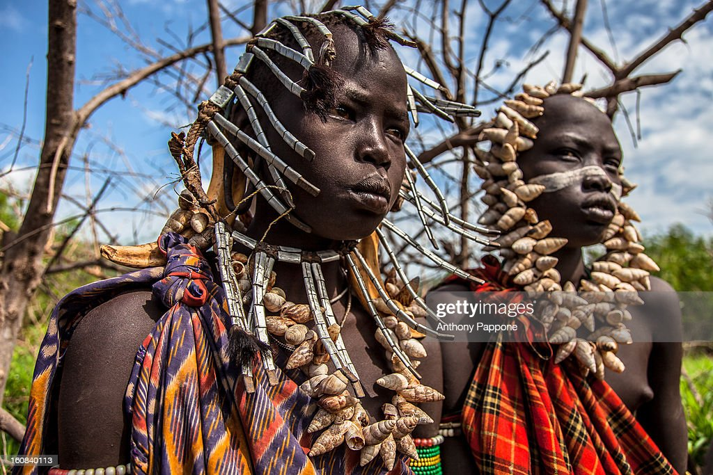 CONTENT] young boys of the tribe Mursi with necklaces of shells in head. the Mursi tribe They are nomadic cattle herders live in the lower Omo Valley inside the mago national park near the Sudanese border. They are famous for its body decoration and ferocious culture. The Mursi women wear big clay plates in their lower lips, and the Mursi men are known for their scarification and for being fierce warriors. The Mursi Tribe is noted for their lip plates, which are made from clay and considered a sign of beauty. Young Mursi girls are pierced at the age 15 or 16 when their lower lips are cut in such a way that the plate can be inserted and then stretched with smaller plates and followed by larger plates. The bigger the plate the more livestock can be brought into the family when she eventually marries.