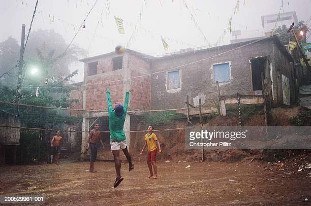 Young boys play a game of Volleyball on a rainy afteroon in a Rio de Janeiro favela, Brazil.