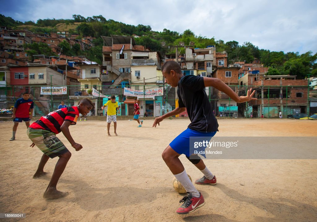 Young boys play football at the Vila Nova Project in the Morro dos Macacos area on October 26, 2013 in Rio de Janeiro, Brazil. The Project Vila Nova was idealized by Alex Sandro and has so far run for 2 years, catering to children and young residents of the Morro dos Macacos area.