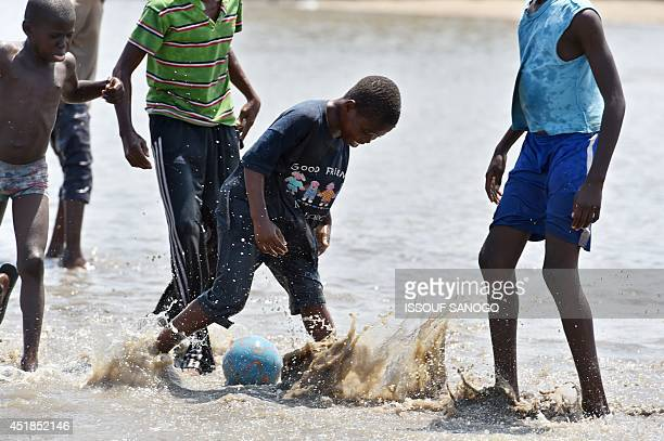 Young boys play football in a flooded street in the Adjoufou district of Abidjan on July 8 following a month of heavy rainfalls over the country's...