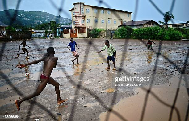 Young boys play football in the rain in Freetown on August 13 2014 The World Health Organisation revealed that the latest death toll from the Ebola...