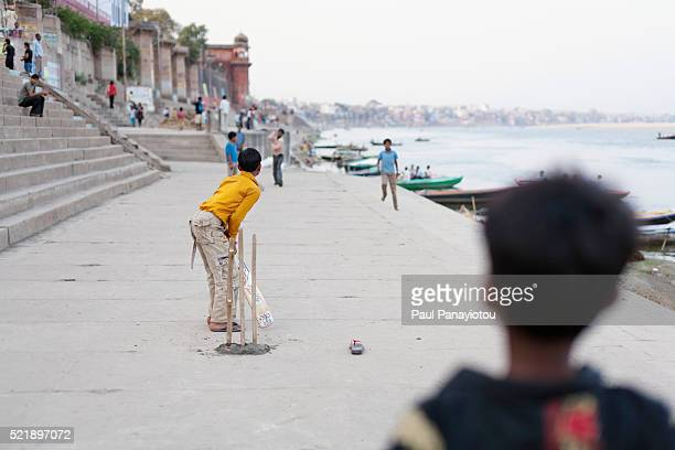 Young boys playing cricket at a ghat by the Ganges river in Varanasi, India