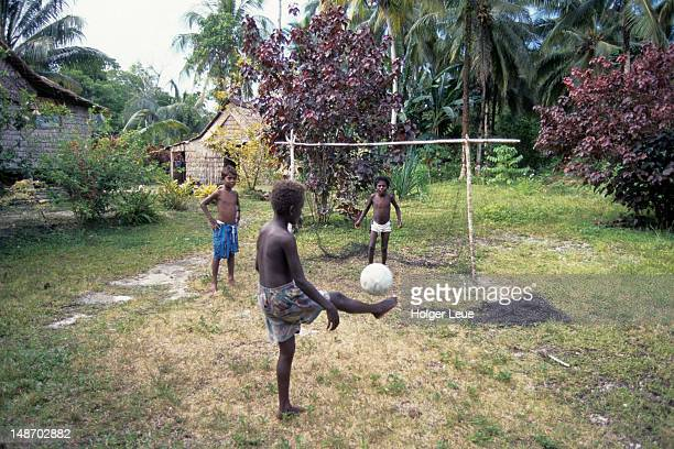 Young boys playing soccer in yard.