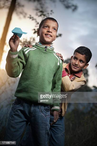 Young boys playing with paper airplane