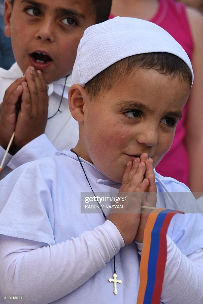Young boys pray as Pope Francis leads an open-air mass in Vartanants Square in Armenia's second-largest city of Gyumri on June 25, 2016. / AFP / KAREN