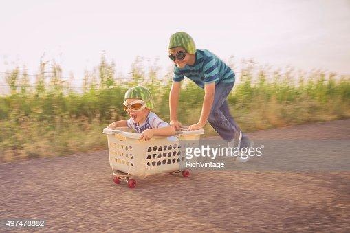 Young Boys Racing on Skateboard Wearing Watermelon Helmets