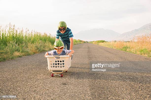 Giovane ragazzo corse su Skateboard indossano caschi di anguria