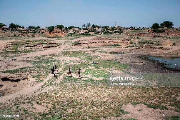 Young boys run and play in and around the heavy erosion caused over the years by mass flooding along the banks of the Zambezi River in Mozambique on...
