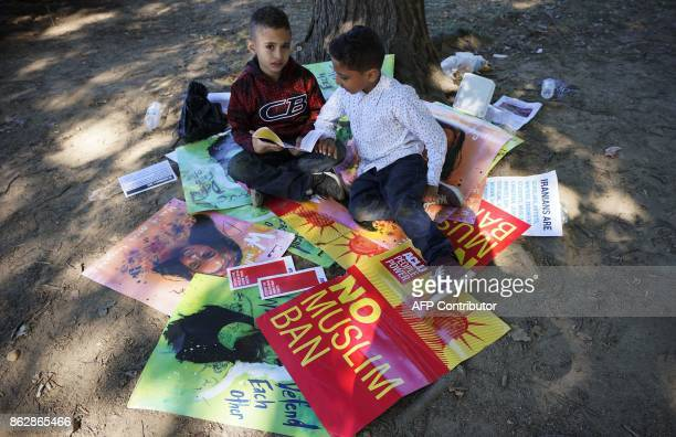 Young boys sit under a tree with placards following a rally against a US President Donald Trump's travel ban in Lafayette Square on October 18 2017...