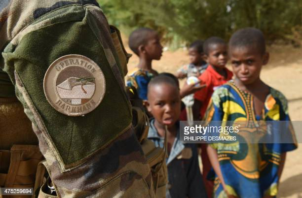 Young boys stand next to a French soldier of Operation Barkhane an antiterrorist operation in the Sahel patrolling in Gao northern Mali on May 30...