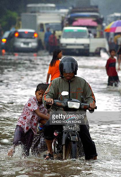 Young boys take advantage of the floods to earn money as they help a motorist through a submerged street in Jakarta 19 February 2004 Hundreds of...