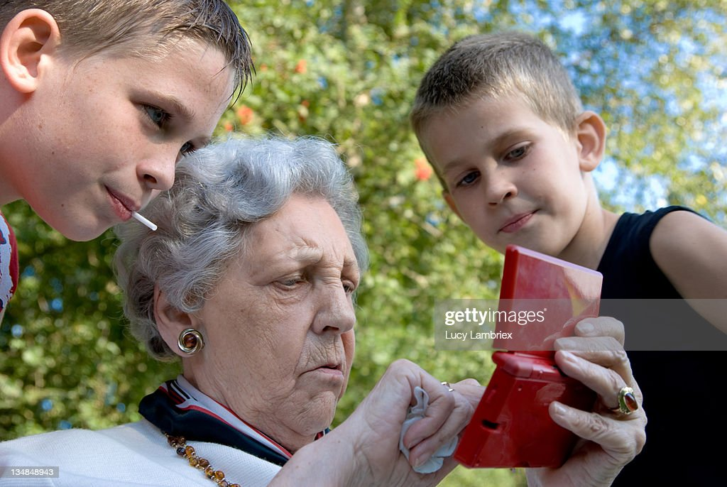 Young boys teaching grandmother to play video game : Stock Photo