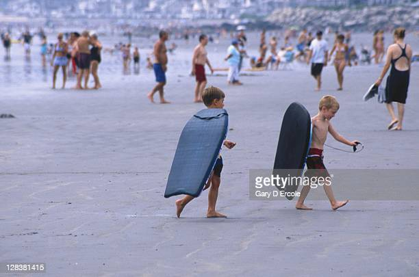 Young boys w/ boogie boards on the beach