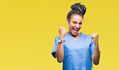 Young braided hair african american girl professional nurse over isolated background very happy and excited doing winner gesture with arms raised, smiling and screaming for success. Celebration concep