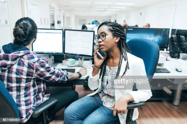 Junge brasilianische Geschäftsfrau telefonieren im Büro