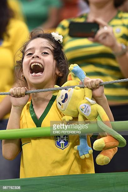 A young Brazilian fan holding the Rio 2016 official mascot Vinicius cheers her team during the men's preliminaries Group A handball match Brazil vs...