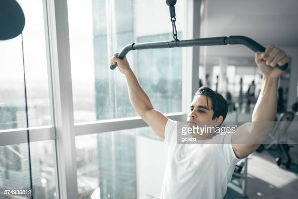young brazilian man pulling weitght at exercise machine