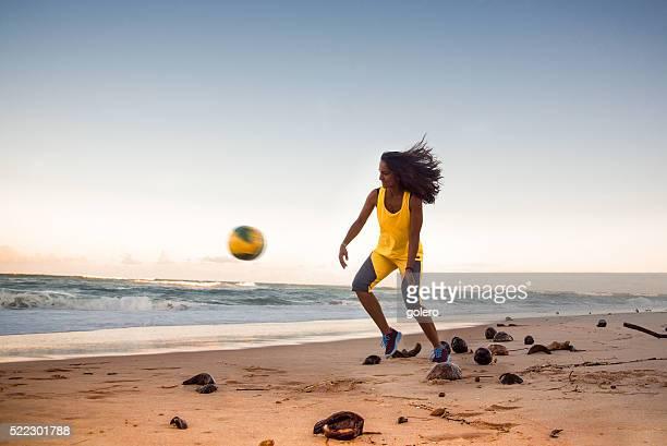 Joven mujer jugando fútbol brasileño playa de puesta del sol horas