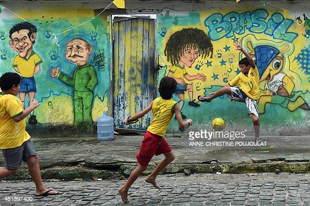 Young Brazilians play football in Porto Seguro on June 28 during the Round of 16 football match between Brazil and Chile played at the Mineirao...