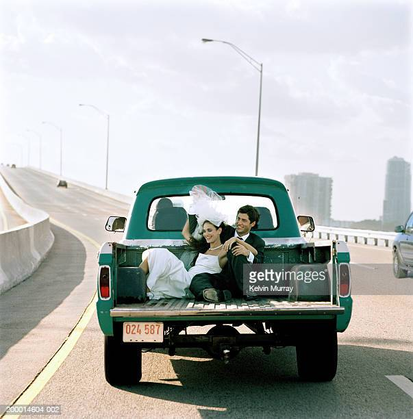 Young bride and groom on back of pick-up truck
