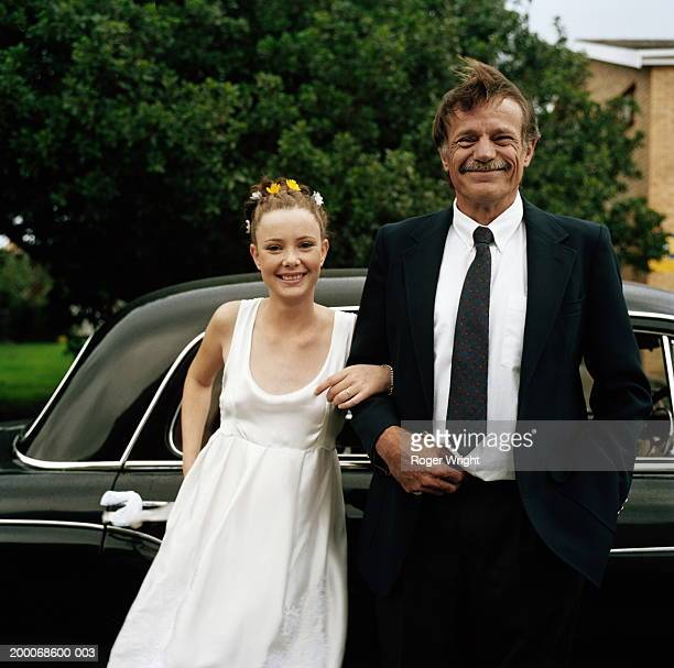 Young bride and mature father standing by car, smiling, portrait
