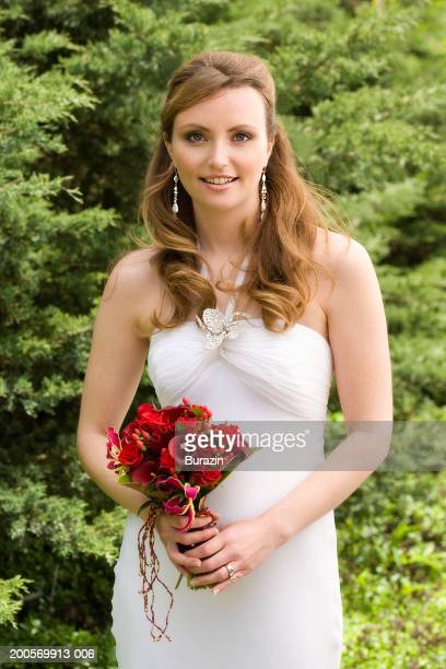 Young bride holding bouquet in garden, smiling, portrait