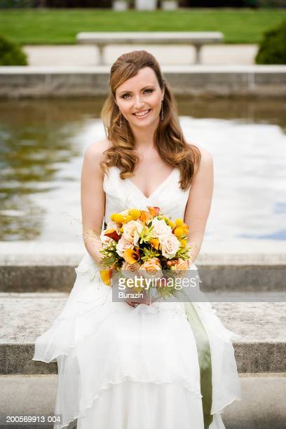Young bride holding bouquet sitting in garden, smiling, portrait