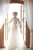 Young bride in gorgeous wedding dress with voluminous skirt looking at window, indoors. Blonde young woman.