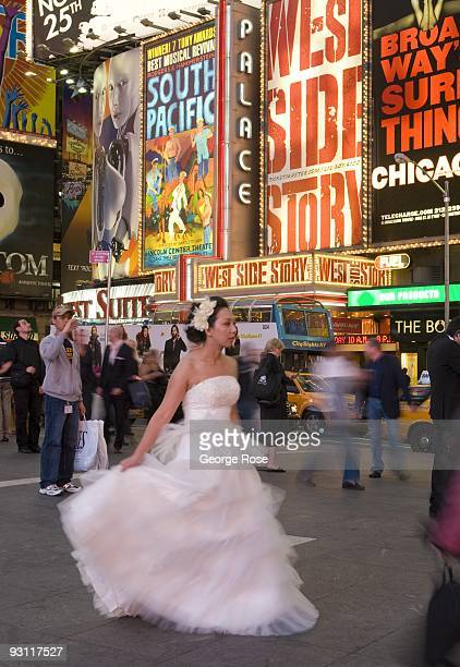 A young bride in her wedding dress walks the streets in Times Square at 7th Ave and Broadway as seen in this 2009 New York NY early evening cityscape...