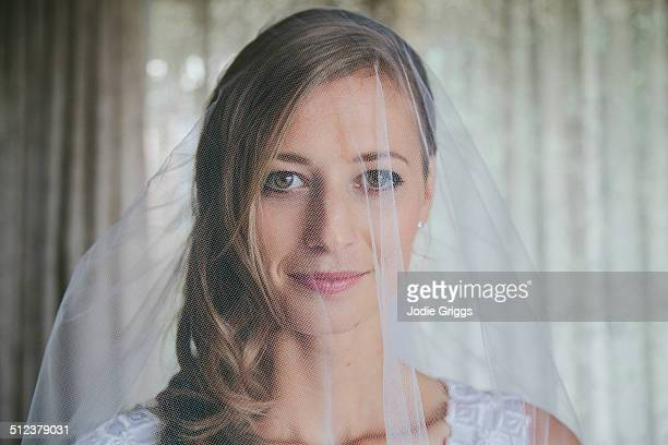 Young bride looking through veil at home