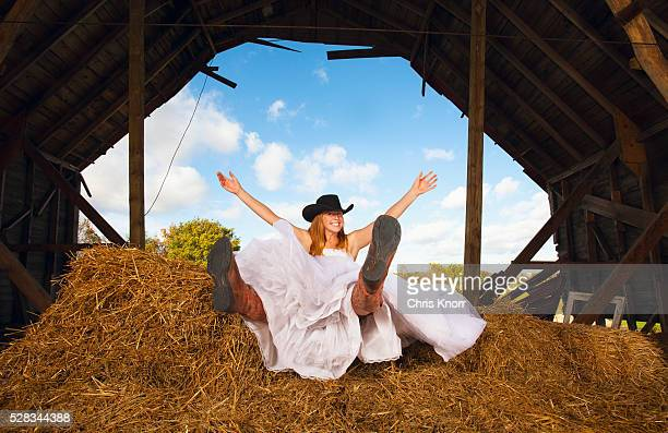 Young Bride Smiling In A Barn With Cowgirl Hat And Boots; Pennock Minnesota United States Of America