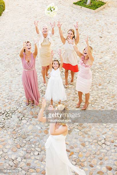 Young Bride Throwing Bouquet Of Flowers At Guests