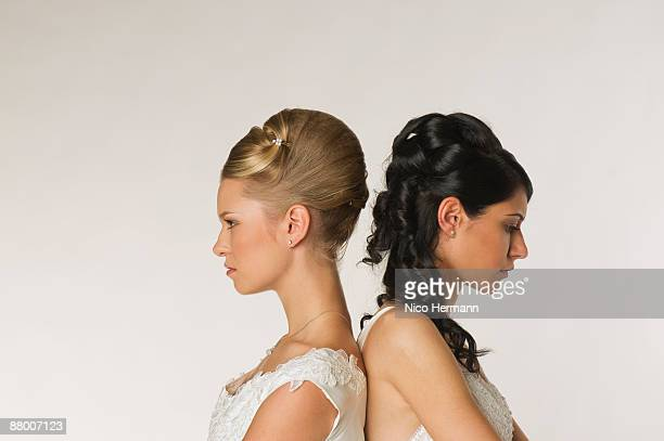 Young brides standing back to back, side view